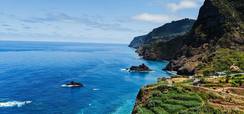 Costa verde pero montañosa de Madeira, con mar azul intenso y cielo despejado.