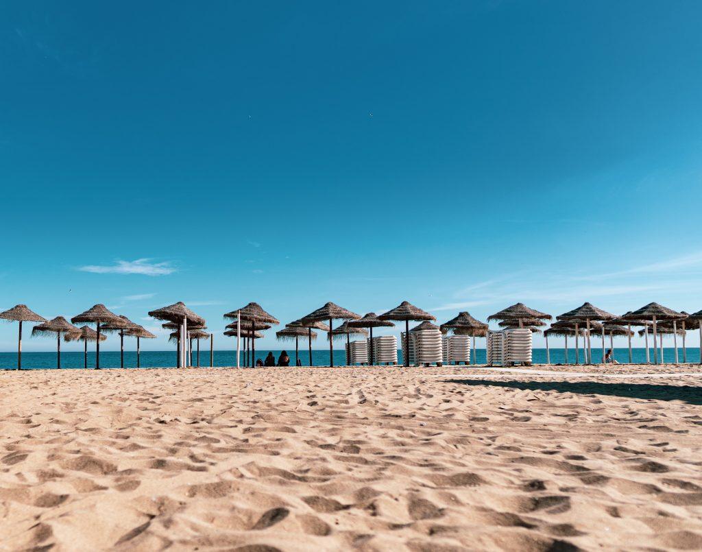 Arena fina y sombrillas de paja en la orilla de la playa de Fuengirola.