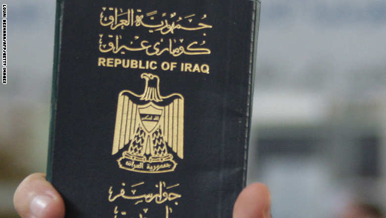 A refugee from Iraq holds his passport a