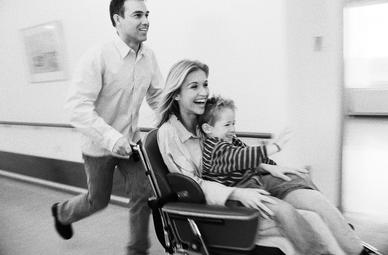 Man pushing wheelchair with woman and child --- Image by © ImageShop/Corbis