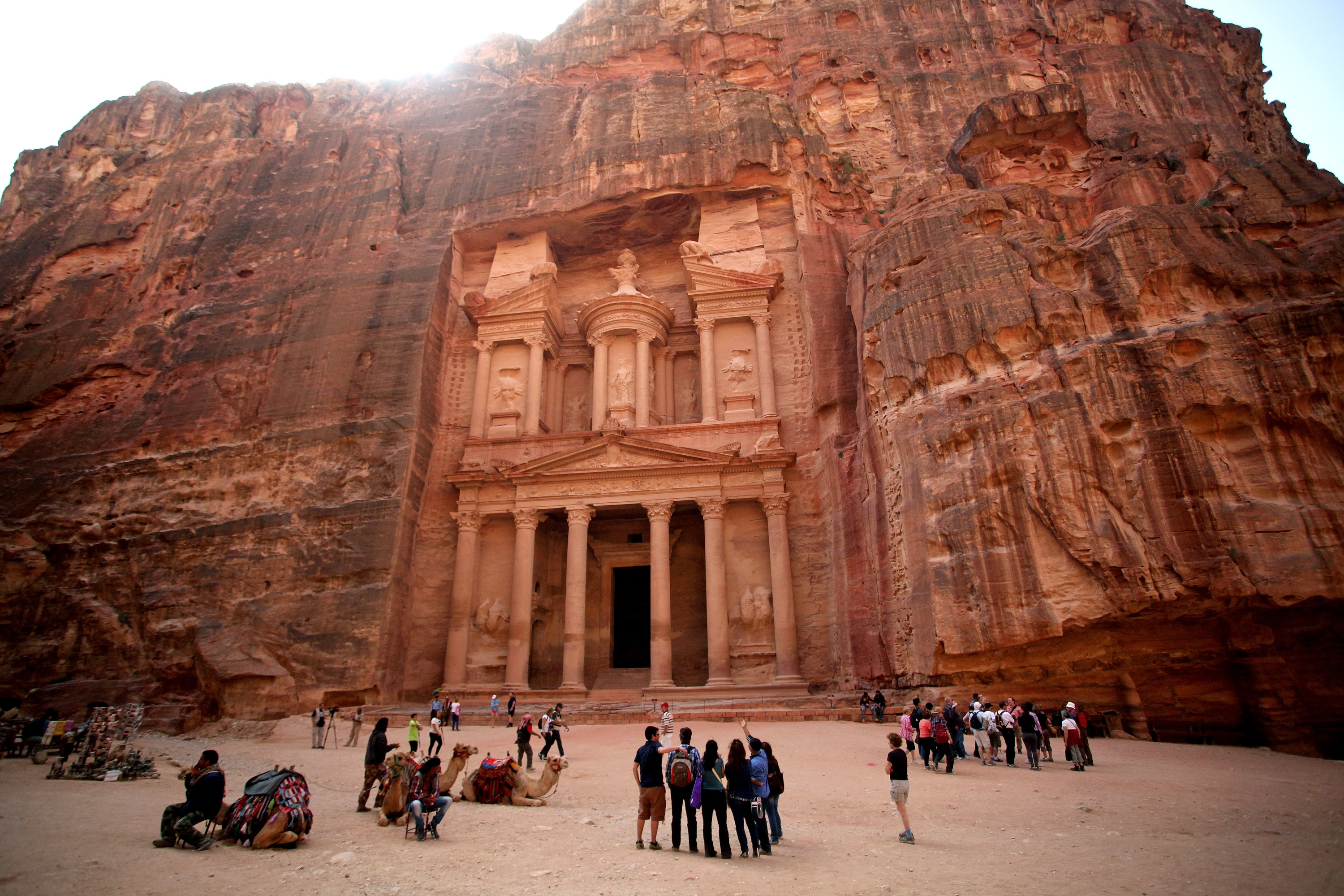In this Thursday, March 6, 2014 photo, tourists stand in front of the rock-hewn Al Khazneh, Arabic for the Treasury, in the ancient city of Petra, Jordan. The kingdom's launched an ecotourism project with the establishment of three camps in the Petra region, the first of 22 proposed eco-camps . The camps will eventually connect three areas in Jordan including the Dana Biosphere Reserve located in south-central Jordan. (AP Photo/Mohammad Hannon)