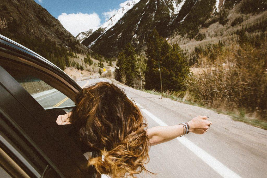 Una chica asomada por la ventana del coche con brazo y melena al viento