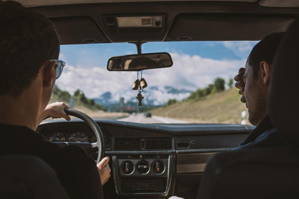 Dos chicos jóvenes de viaje en coche.