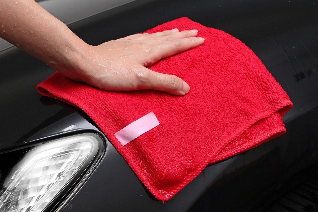 Mano con una balleta roja limpiando un coche