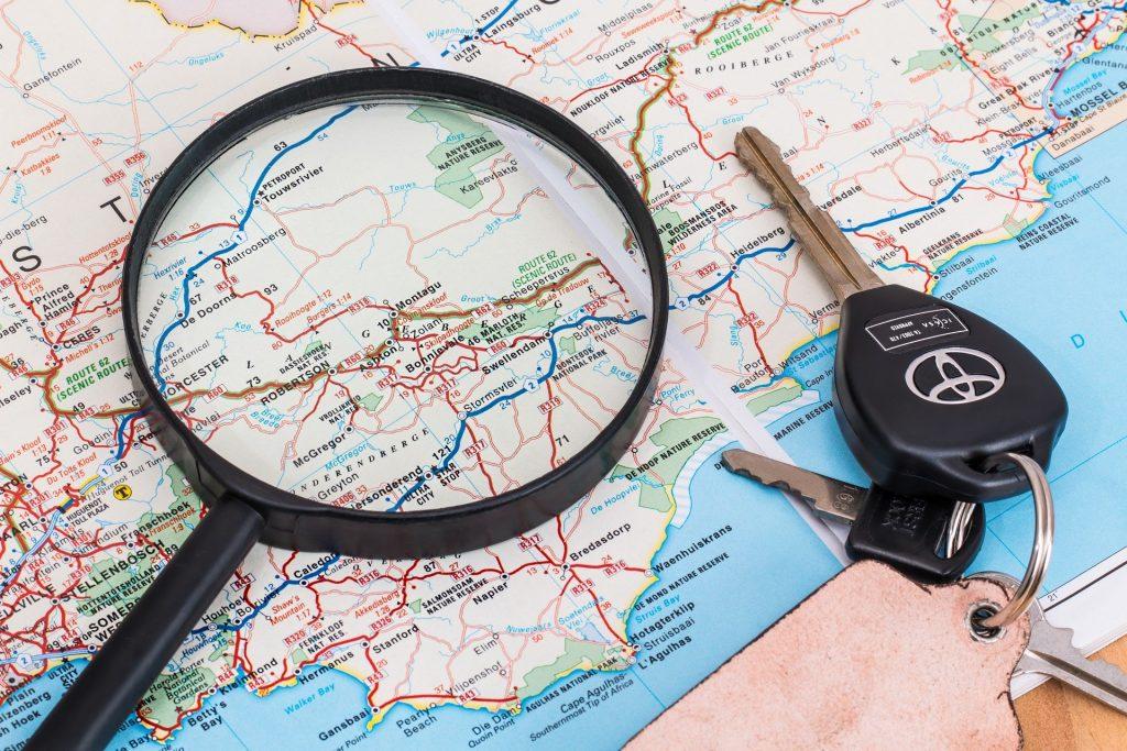 Lupa y llavero con llaves de coche sobre mapa