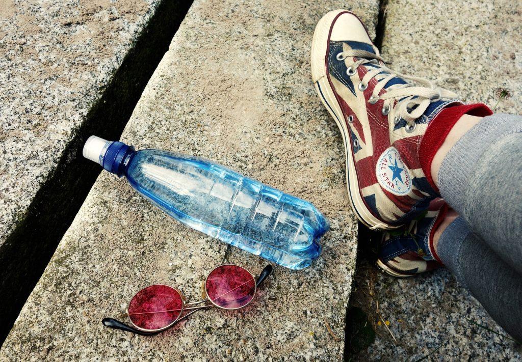 Pies de alguien con zapatillas converse, una botella de agua y unas gafa rojas sobre suelo de piedra