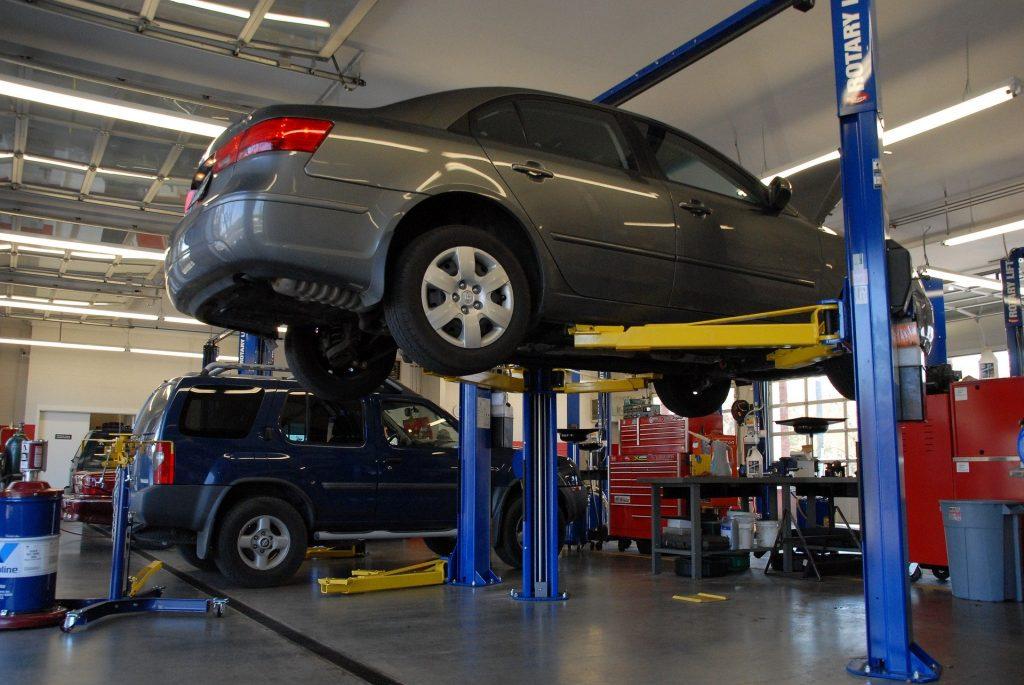 Coche gris elevado en un taller de automóviles.