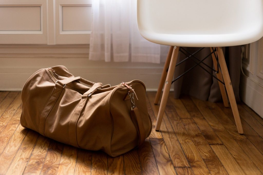 Una silla blanca y una bolsa de viaje beige en una habitación con suelos de madera