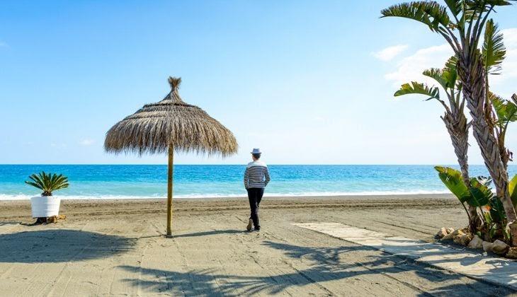 Señor mirando al mar junto a una sombrilla de paja, en la orilla de la playa de Torre del Mar, en la costa del sol