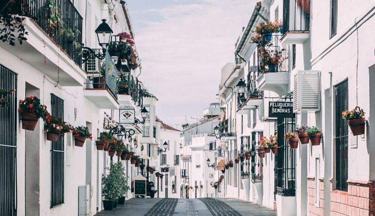 imagen de las calles de Coín con casas blancas y flores en las ventanas