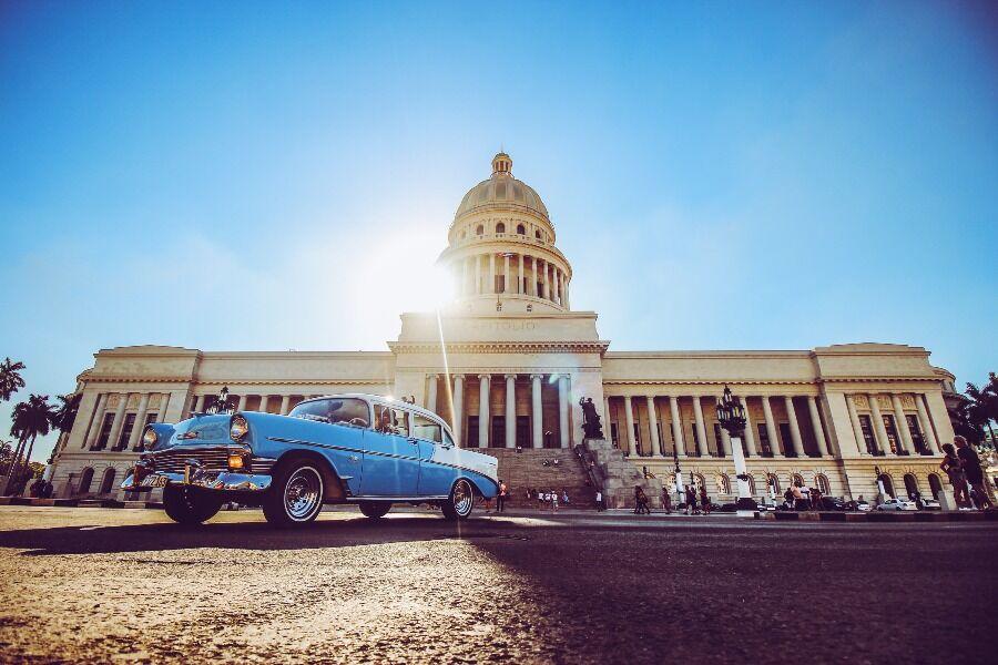 Coche azul clásico frente al Capitolio de la Habana
