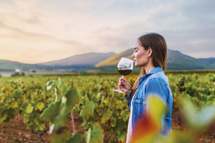 Mujer con una copa de vino entre viñedos.