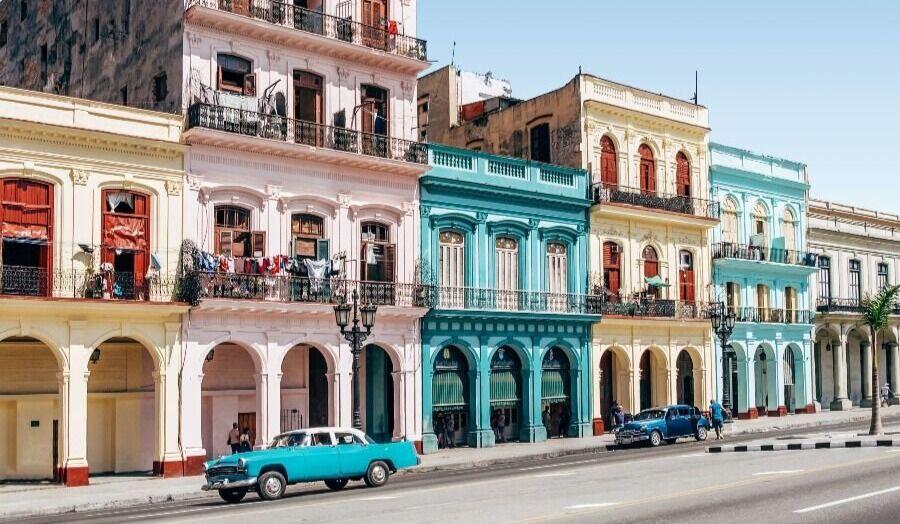 Coches clasicos en las calles de la habana con casas de colores al fondo