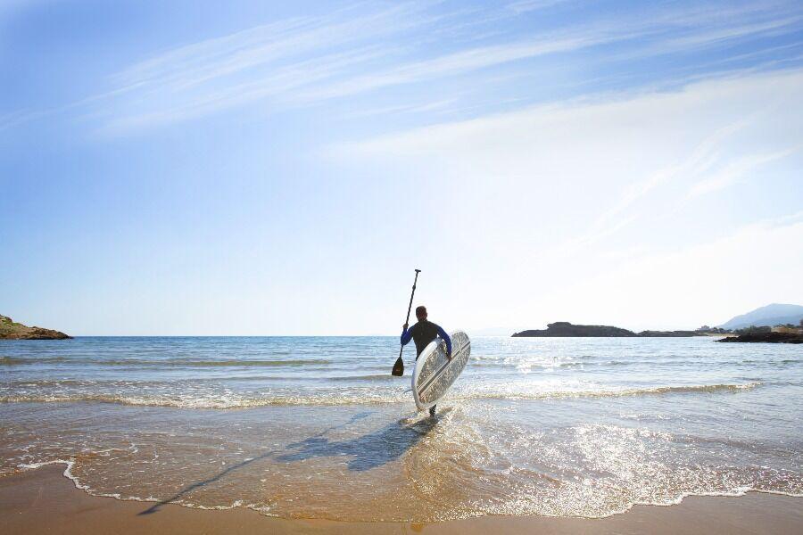 Hombre adentrandose en el mar de Percheles, Mazarrón, con equipación de paddle surf.