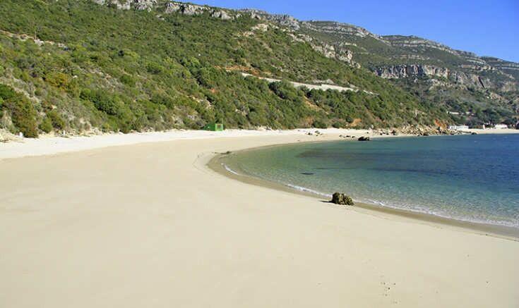 Playa de Arrábida con arena blanca y vegetación al fondo, Portugal.