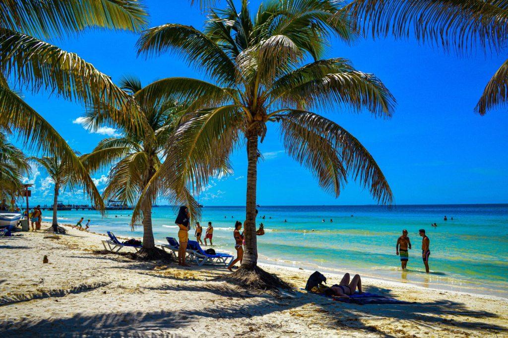 Gente bajo la sombra de una palmera en la playa de Cayos Blancos, Cuba.