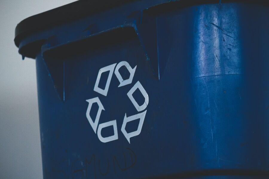 Contenedor de reciclaje azul con el símbolo en blanco.