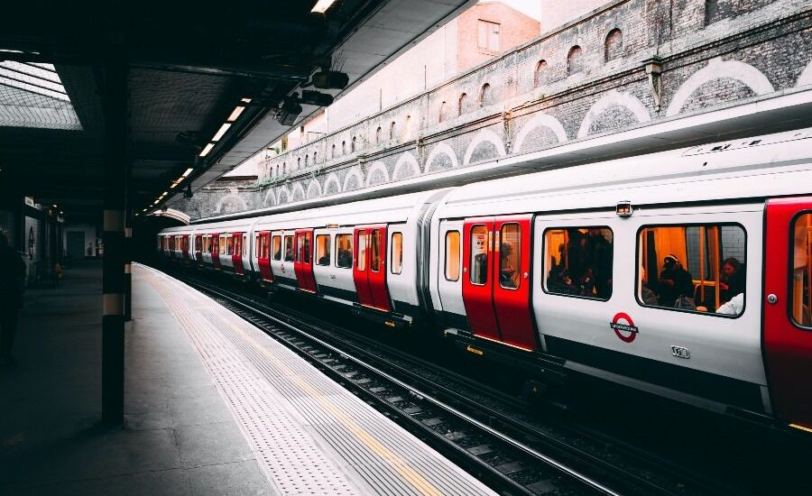 Metro de Londres rojo y blanco en estación abierta.